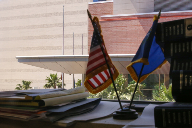 Flags sit on a window sill in an office across from the Regional Justice Center, where flags were being flown at half-staff almost two weeks after they were supposed to be raised to full-staff, in ...