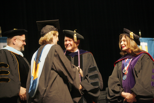 Dr. Ray Alden shakes a student's hand at Touro University Nevada's graduation ceremony alongside Rabbi Fromowitz, left, and former Congresswoman Shelley Berkley, right, at the Rio Hotel and Casino ...