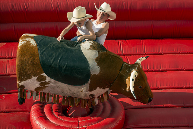 Garret Geitz, 8, helps his brother Ryden, 5 get up on a mechanical bull at Las Vegas Helldorado Days within the Las Vegas Village on Friday, May, 13, 2016. Jeff Scheid/Las Vegas Review-Journal Fol ...