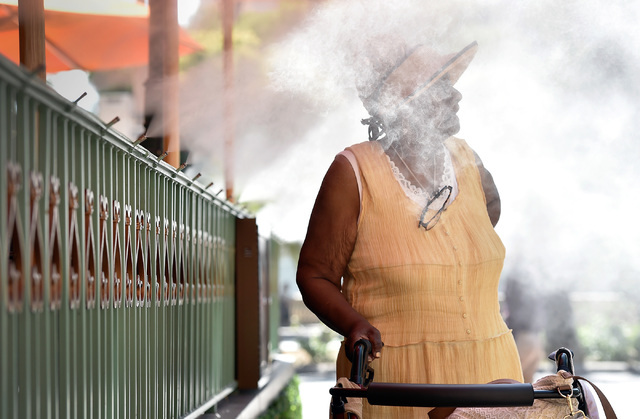 Tourist Eva Wiggins of Penn, stands in a cool mist as takes a moment as she walks along the Strip Tuesday, May 31, 2016, in Las Vegas. Forecasters said temperatures will continue to rise with a 10 ...