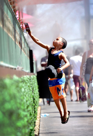 Troy Gray of Ga. jumps to reach the cool mist as he walks along the Strip with his family Tuesday, May 31, 2016, in Las Vegas. Forecasters said temperatures will continue to rise with a 101-degree ...