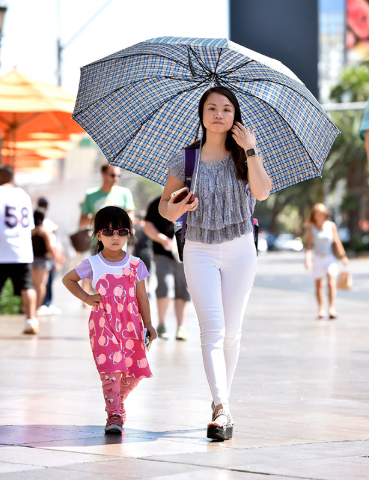 Tourists make their own shade as they stroll along the Strip Tuesday, May 31, 2016, in Las Vegas. Forecasters said temperatures will continue to rise with a 101-degree high on Wednesday, which is  ...