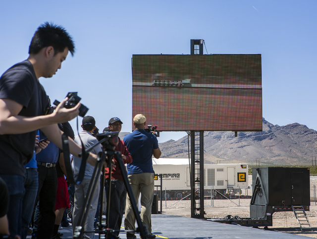 Media and invited guests view a video replay of the Hyperloop One test vehicle propelling down a set of tracks during the first public test of Hyperloop's transit technology at Apex on Wednesday,  ...