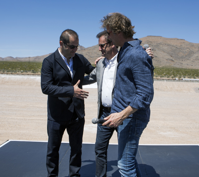 Hyperloop One executives Shervin Pishevar, left, co-founder, executive chairman, Rob Lloyd, CEO, and Brogan Bam Brogan, chief technology officer, congratulate each other after their first public t ...