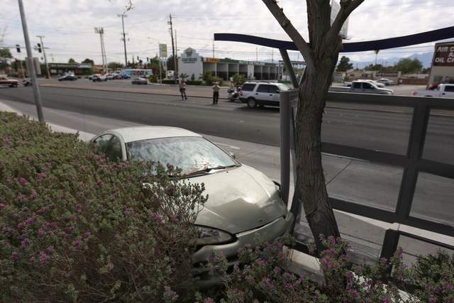 Las Vegas police investigate the scene of a fatal accident where a car hit a bus stop near the intersection of Decatur Boulevard and Smoke Ranch Road in Las Vegas on Thursday, May 5, 2016. (Brett  ...