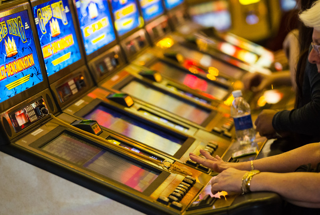 People play on slot machines in this file photo.