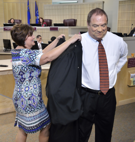 Rodney Burr gets some help from his wife Annette during a robing ceremony after he was sworn in as municipal judge at Henderson City Hall at 240 S. Water St. in Henderson on Tuesday, May 17, 2016. ...