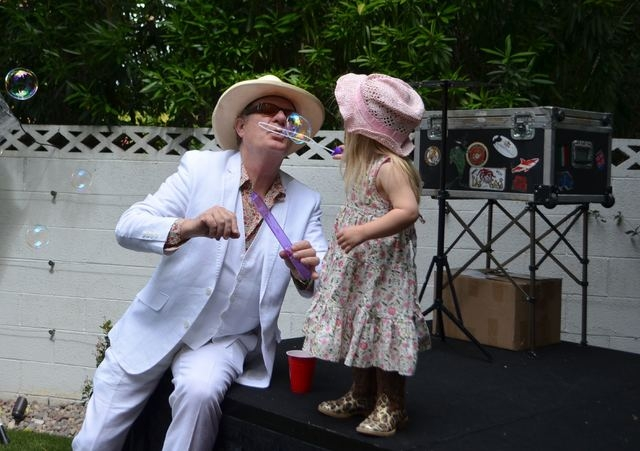 Rancho Bel Air resident Warwick Stone blows bubbles for his daughter Charlotte, 2, at Mac King's 16th Kentucky Derby Party May 7, 2016. Ginger Meurer/Special to View