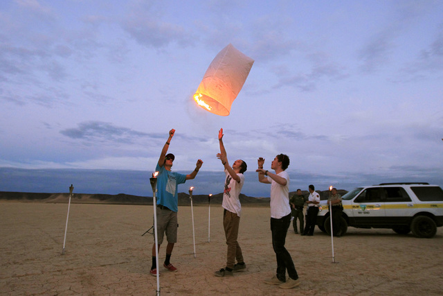 From left, J.D. Hansen, Mason Burt and Will Smith release a paper lantern as they, public lands officials and event organizers test them and their environmental impact in advance of the RiSE Festi ...