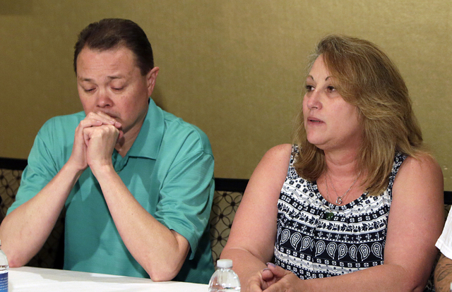 Lee's Discount Liquor robbery victim Matthew Christensen's mother, Theresa, speaks about the death of her son as her husband, Dennis, looks down as they address the media at Excalibur on Thursday, ...