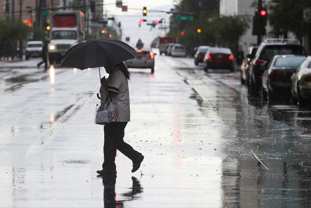 A woman crosses Bridger Avenue during a rainstorm in downtown Las Vegas on Friday, May 6, 2016. (Brett Le Blanc/Las Vegas Review-Journal) Follow @bleblancphoto)