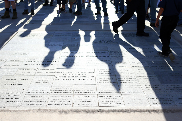 Shadows are cast on memorial plaques prior to the 26th annual placement of flags at Southern Nevada Veterans Memorial Cemetery in Boulder City, Nev. on May 28, 2016. More than 26,000 flags were pl ...
