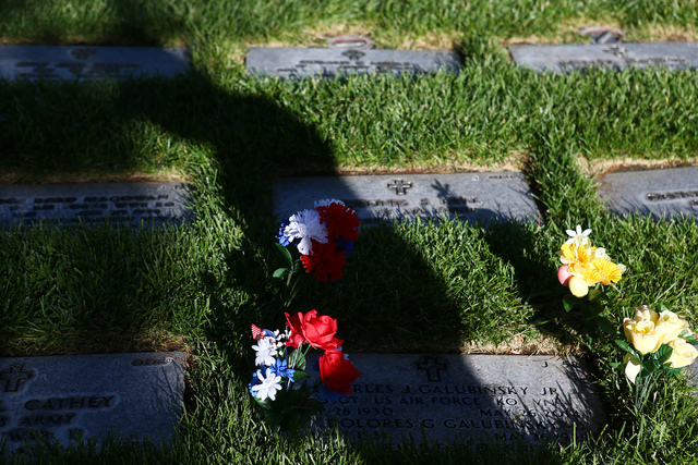 A shadow is cast on red, white and blue flowers prior to the 26th annual placement of flags at Southern Nevada Veterans Memorial Cemetery in Boulder City, Nev. on May 28, 2016. More than 26,000 fl ...