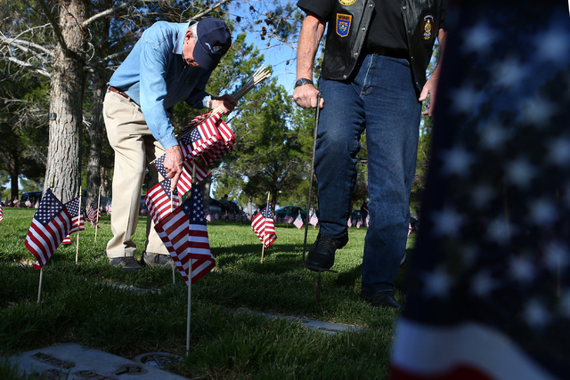 Cold War veteran Gary Parriott places flags in part of 26th annual placement of flags at Southern Nevada Veterans Memorial Cemetery in Boulder City, Nev. on May 28, 2016. Over 26,000 flags were pl ...