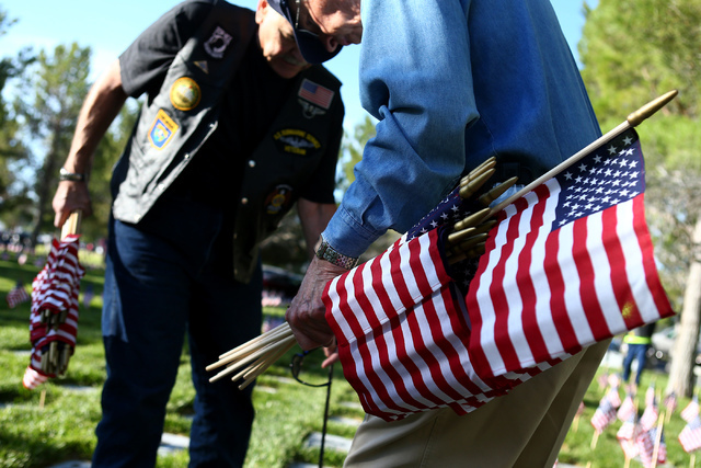 Cold War veteran Gary Parriott carries a bundle of flags in part of the 26th annual placement of flags at Southern Nevada Veterans Memorial Cemetery in Boulder City, Nev. on May 28, 2016. More tha ...