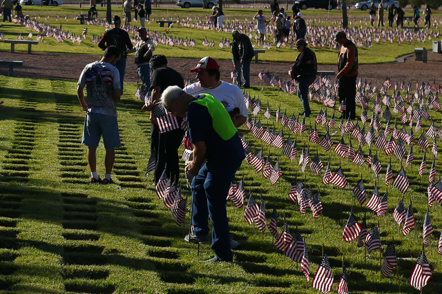 Volunteers place flags in part of the 26th annual placement of flags at Southern Nevada Veterans Memorial Cemetery in Boulder City, Nev. on May 28, 2016. More than 26,000 flags were placed in less ...