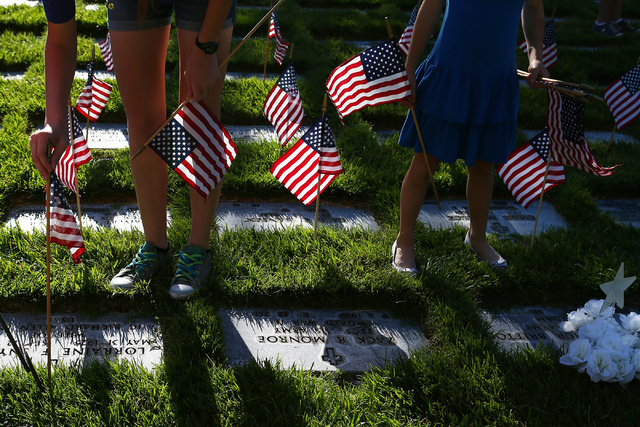 Faith,16, and Bella White, 7, place flags in part of the 26th annual placement of flags at Southern Nevada Veterans Memorial Cemetery in Boulder City, Nev. on May 28, 2016. (Bridget Bennett/Las Ve ...