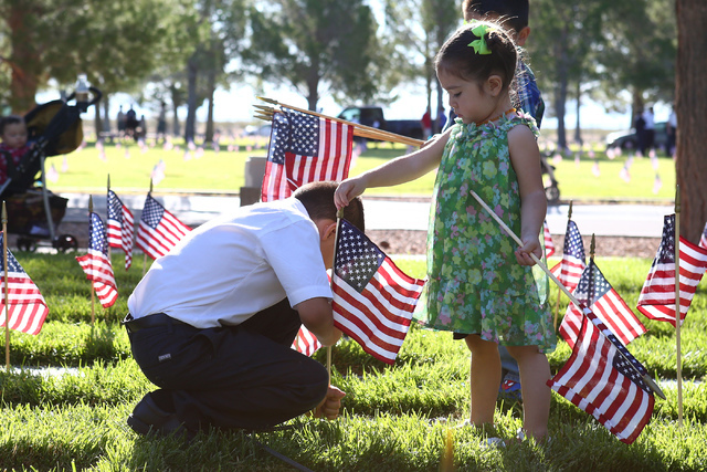 Siblings Ezra and Evelyn White help place flags in part of the 26th annual placement of flags at Southern Nevada Veterans Memorial Cemetery in Boulder City, Nev. on May 28, 2016. (Bridget Bennett/ ...