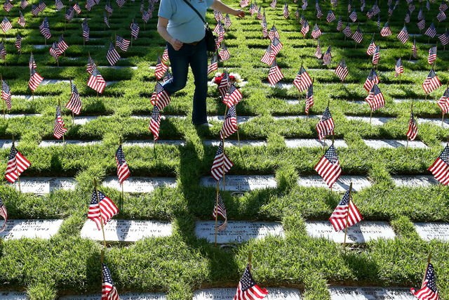 Linda Miller carefully passes by flags during the 26th annual placement of flags at Southern Nevada Veterans Memorial Cemetery in Boulder City, Nev. on May 28, 2016. More than 26,000 flags were pl ...