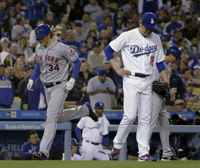 New York Mets' Noah Syndergaard, left, rounds the bases on a three-run home run as Los Angeles Dodgers starting pitcher Kenta Maeda looks down during the fifth inning of a baseball game in Los Ang ...