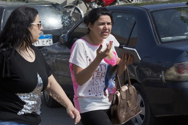 An Egyptian, who said her brother among passengers, grieves as she leaves the Egyptair in-flight service building where relatives are being held at Cairo International Airport, Egypt, Thursday, Ma ...
