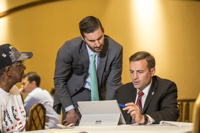 Adam Laxalt, Nevada attorney general, right, and Wes Duncan, first assistant attorney general, work with James Dorsey and Doris Haynes to assist them with their will during a military appreciation ...