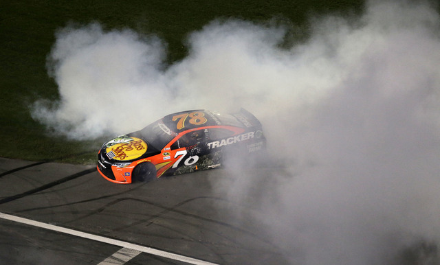 Martin Truex Jr. (78) does a burnout after winning the NASCAR Sprint Cup Series auto race at the Charlotte Motor Speedway in Concord, N.C., Sunday, May 29, 2016. (Gerry Broome/The Associated Press)