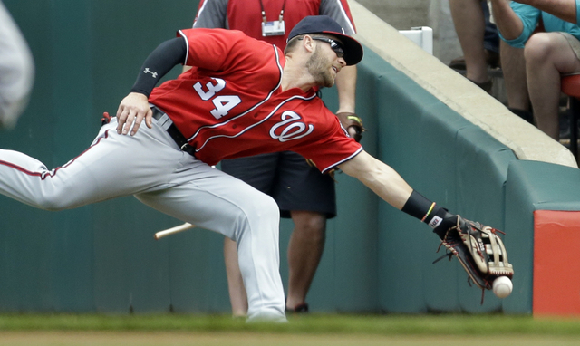 Washington Nationals right fielder Bryce Harper is unable to catch a foul ball hit by St. Louis Cardinals' Matt Holliday during the first inning of a baseball game Sunday, May 1, 2016, in St. Loui ...