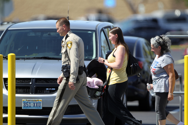 Las Vegas police escort people outside a Walmart after shootings left five people dead -- including two Las Vegas police officers -- at the store and a nearby CiCi's Pizza at the corner of North N ...