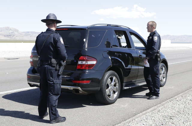 Nevada Highway Patrol trooper Jeff Freeman talks to a driver who was pulled over for failing to move over for stopped patrol car on I-15 North in Jean as trooper Jason Buratczuk, left, looks on Fr ...