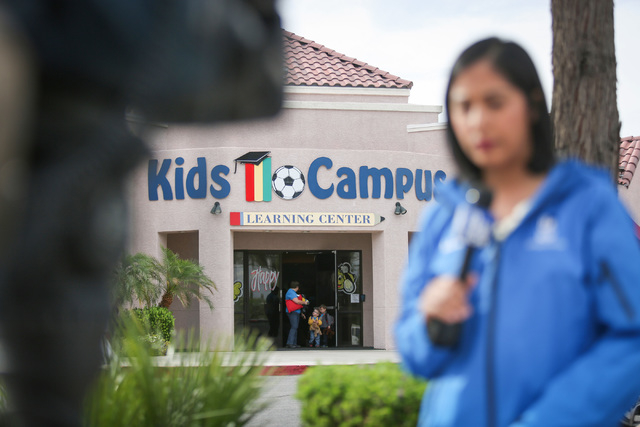 A family walks out of Kids Campus daycare as a TV reporter gives a live report in North Las Vegas on Friday, May 6, 2016. On Thursday, police say Travis Spitler shot and killed his ex-girlfriend C ...