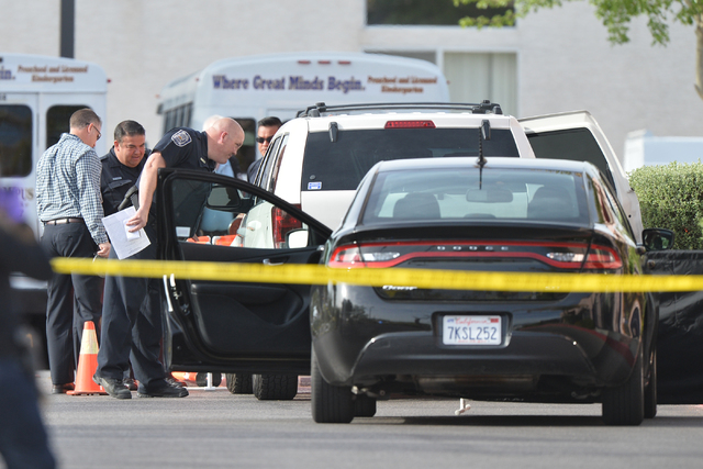 North Las Vegas police peer into a car while investigating a fatal shooting at a day care center at Martin Luther King Boulevard and Ramble Ridge Way on Thursday, May 5, 2016. (Brett Le Blanc/Las  ...