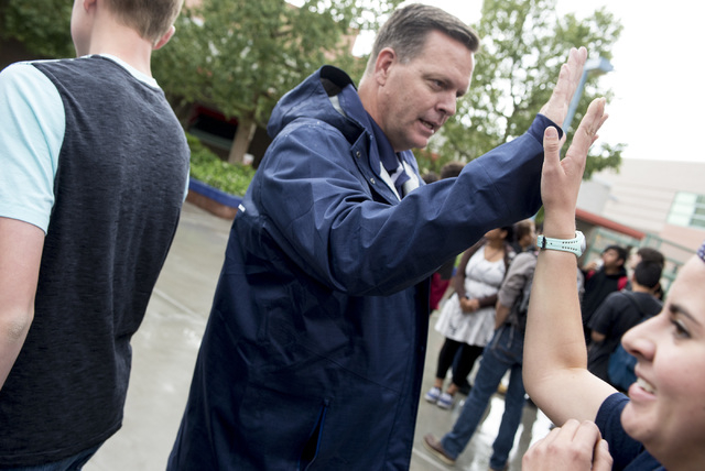 Shadow Ridge High School principal Travis greets students with high-fives as they make their way to lunch May 6, 2016. Warnick was named a finalist of Varsity Brands 2016 School Spirit Awards Prin ...