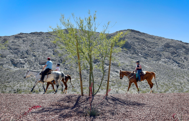 Horseback riders from left, T.J. Griffin, Amanda Griffin and Aubrey Griffin ride the trail around Lone Mountain Tuesday, May 3, 2016, in Las Vegas. The trail is part of the Lone Mountain Equestria ...
