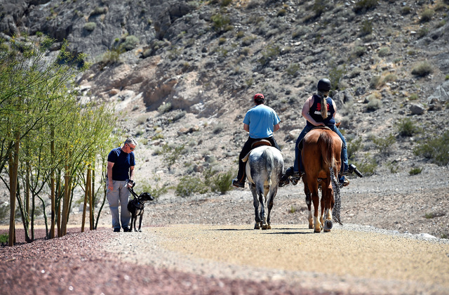 Mahlon Edwards, left, and his dog, Jake, watch as horseback riders T.J. Griffin, Amanda Griffin and Aubrey Griffin ride by at the Lone Mountain Equestrian Park and Trail Tuesday, May 3, 2016, in L ...