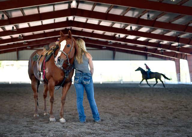 Joey Griffith, holding her mare, Juicy, watches her mother, Kelly Griffith ride in the covered arena at the Lone Mountain Equestrian Park and Trail Tuesday, May 3, 2016, in Las Vegas. David Becker ...