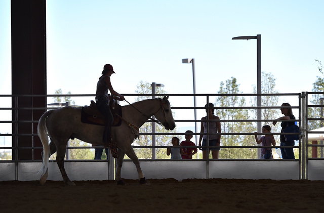 Reagan Purvis, aboard her horse, Trouper, rides up to visitors in the covered arena at the Lone Mountain Equestrian Park and Trail Tuesday, May 3, 2016, in Las Vegas. David Becker/View