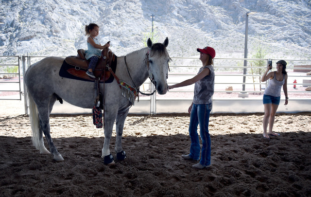 Penelope Calvillo, 2, left, takes a ride aboard Reagan Purvis' horse, Trouper, as Calvillo's mother, Vanessa Calvillo, right, photographs the special moment in the covered arena at the Lone Mounta ...
