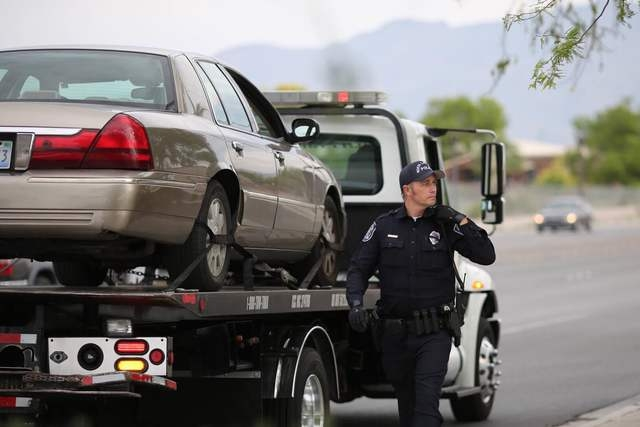 A North Las Vegas police officer walks past a car on North Fifth Streetnear Craig Road that police say was involved in a fatal shooting, which may have stemmed from a road-rage incident, Friday, ...