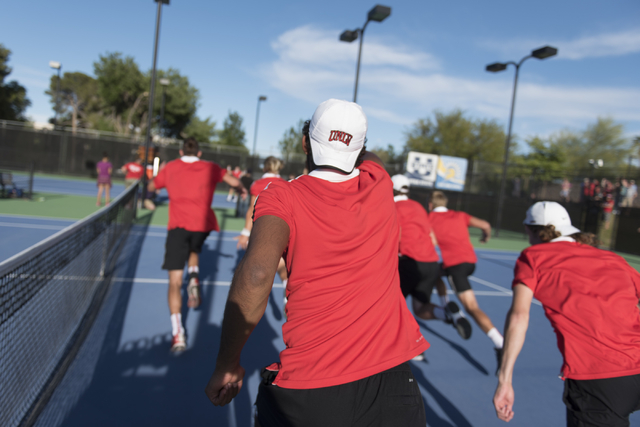 UNLV players rush onto the court to greet Richard Solberg following his win to take the Mountain West Conference men's tennis championship title at UNLV's Fertitta Tennis Complex in Las Vegas Sund ...