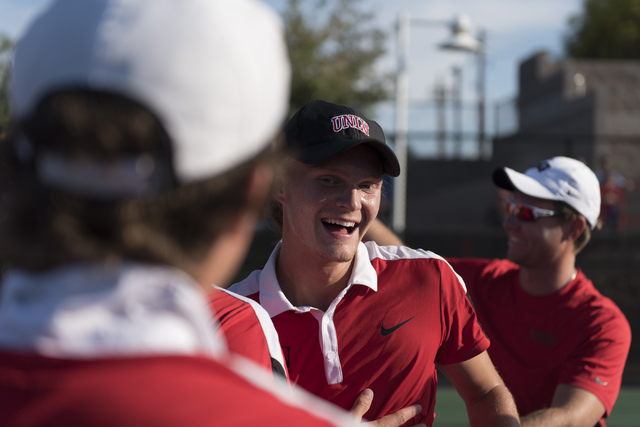 UNLV's Richard Solberg, center, is rushed by teammates following his win to take the Mountain West Conference men's tennis championship title at UNLV's Fertitta Tennis Complex in Las Vegas Sunday, ...