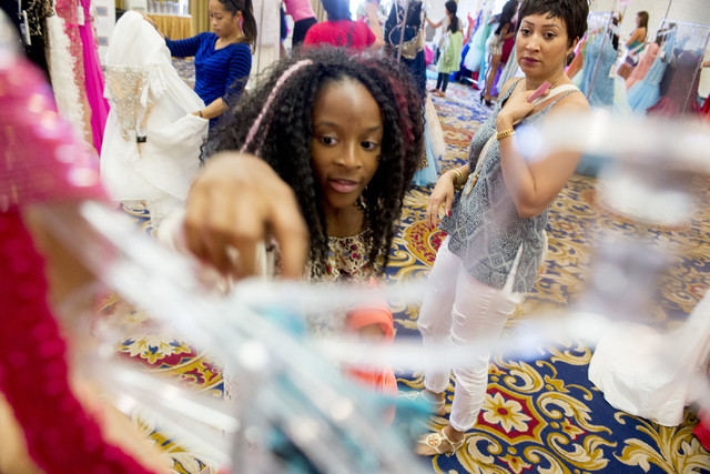 Anaiya Thompson and her mom, Ayesha Thompson, look for dresses during Operation That's My Dress, hosted by the USO in conjunction with Miss USA, at Bally's in Las Vegas on May 28, 2016. Bridget Be ...