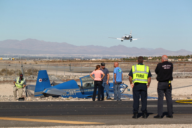 Officials from the Clark County Department of Aviation, Clark County Fire Department, Henderson Fire Department and Henderson Police Department respond to an airplane crash at the southern edge of ...