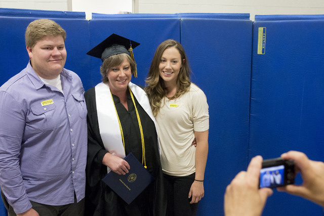 Inmate Alica Wegner, center, takes a photo with her children Justin and Jaclyn after receiving her bachelor's degree at the Florence McClure Women's Correctional Center's graduation ceremony in La ...