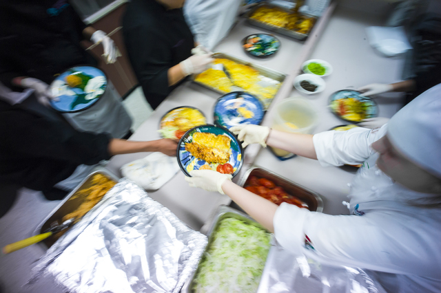Sophomore Carter Overland, left, passes a dish to senior Lauren Morell as students get ready to serve lunch as part of the ProStart program at Silverado High School, 1650 Silver Hawk Ave., May 5,  ...