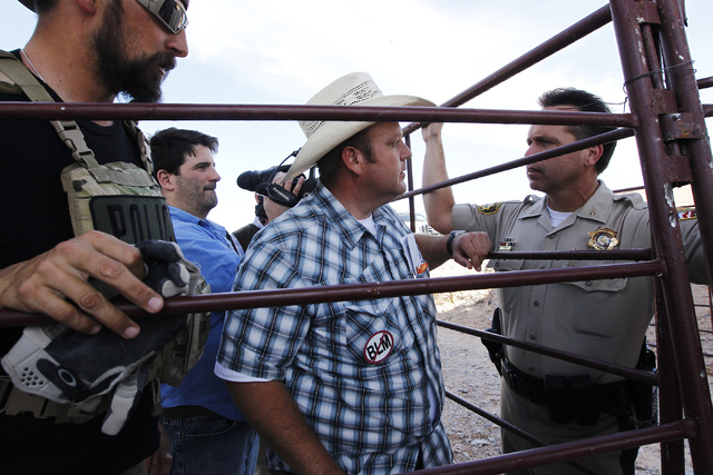 Dave Bundy, middle, talks with Las Vegas Metro Police Chief Deputy Tom Roberts, right, while trying to convince the BLM to release their impounded cattle outside of Bunkerville on April 12, 2014.  ...