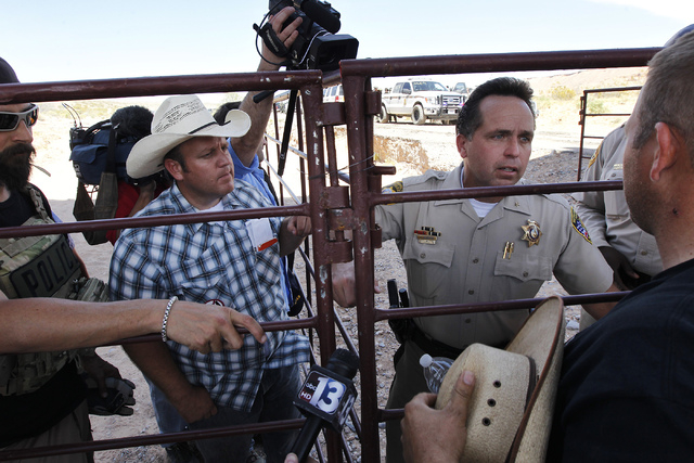 Dave Bundy, left, and his brother Ammon Bundy, far right, talk with Las Vegas Metro Police Chief Deputy Tom Roberts while trying to convince the BLM to release their impounded cattle outside of Bu ...