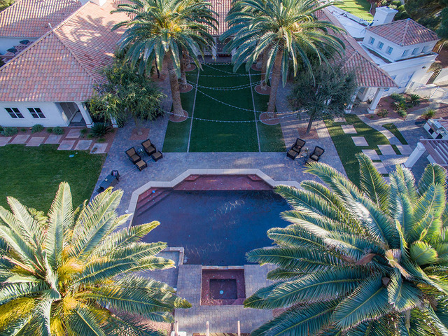 Mature palm trees line a backyard pathway across to the pool and spa, which is positioned in the center of the large yard, big enough to host a gathering of hundreds. (Napoli Group)