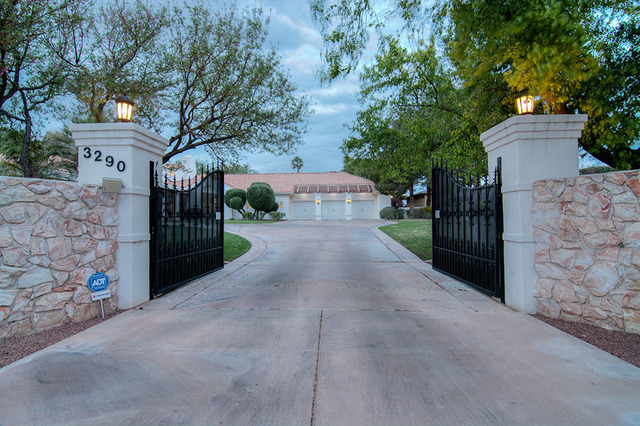 The house sits behind a pair of iron gates and has a welcoming entrance with waterfall, lush landscaping and a circular drive leading to a porte-cochere. (Napoli Group)