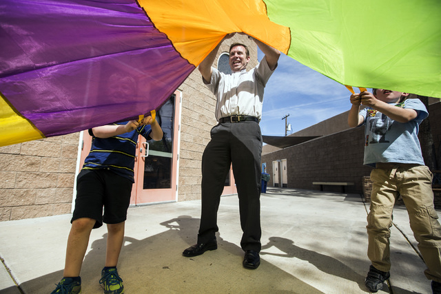 The Rev. Michael Engfer plays a parachute game with students at All Saints Episcopal Church, 4201 W. Washington Ave. Engfer, serves both All Saints Episcopal Church and the Air Force Reserves as a ...